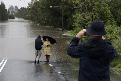 Un hombre toma una foto de una pareja de pie al borde de una carretera inundada por el agua del río Hawkesbury en Windsor (AP Photo/Rick Rycroft)
