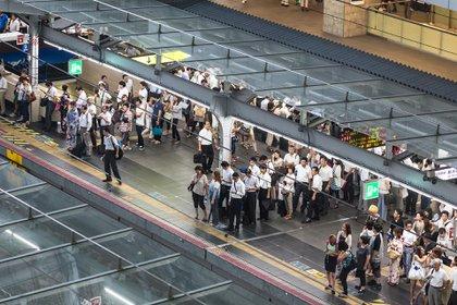 Las personas aguardan la llegada del tren en Osaka haciendo fila ordenadamente (Shutterstock)