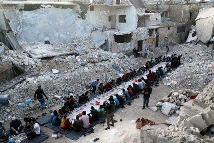 Personas comen su comida Iftar, Atarib, zona rural de Alepo, Siria, 7 mayo 2020 REUTERS/Khalil Ashawi