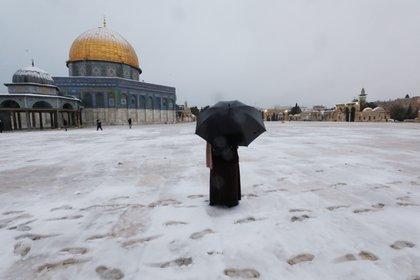 Una mujer junto a la Cúpula de la Roca en el complejo conocido por los judíos como el Monte del Templo y por los musulmanes como el Noble Santuario durante una mañana nevada en la Ciudad Vieja de Jerusalén, el 18 de febrero de 2021. REUTERS / Ammar Awad