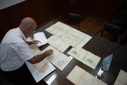 El Contraalmirante Marcelo Tarapow despliega con orgullo algunos de los planos que el propio Ingeniero Luiggi dibujara para la construcción de los diques de la base naval