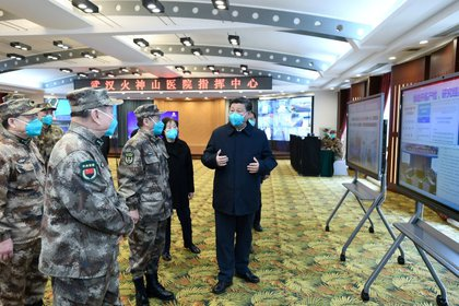 El presidente de China, Xi Jinping, habla con un equipo médico durante su visita a pacientes de coronavirus en Wuhan.  March 10, 2020. Xie Huanchi/Xinhua via REUTERS. ATENCIÓN EDITORES: ESTA IMAGEN FUE PROVISTA POR UNA TERCERA PARTE.