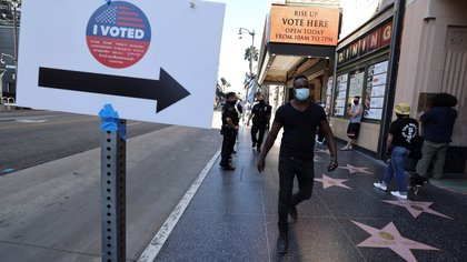 People walk on Hollywood Boulevard outside the Pantages Theater polling station, during the global outbreak of the coronavirus disease (COVID-19), in Hollywood, Los Angeles, California, U.S., October 30, 2020. REUTERS/Lucy Nicholson
