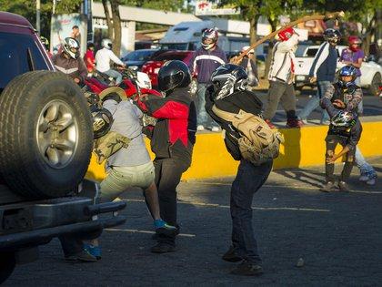 Dos miembros de las fuerzas antichoque agreden a una persona durante las protestas en contra de las reformas del Instituto Nicaragüense de Seguridad Social (INSS), en Managua(EFE/Jorge Torres)