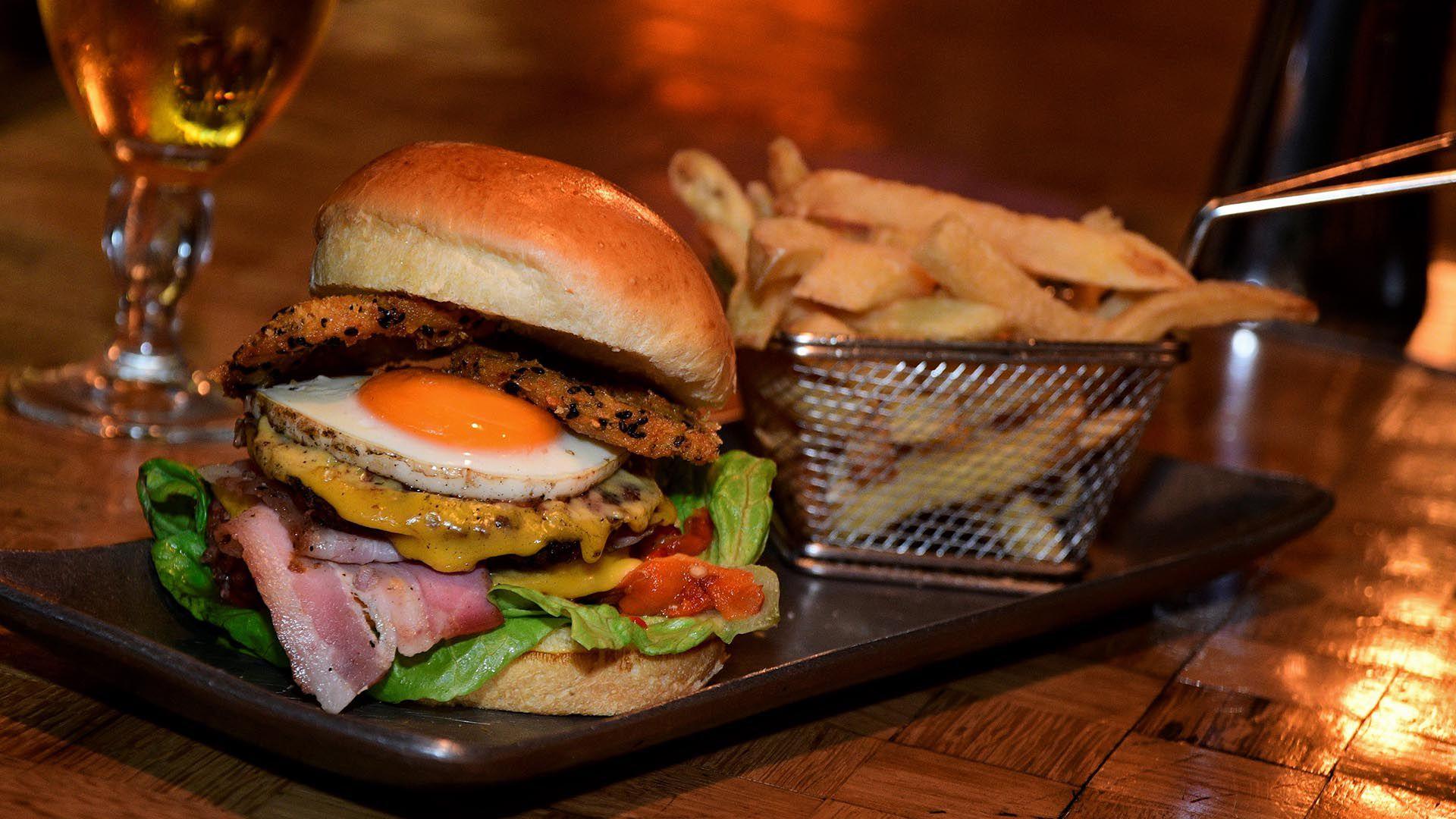 Una hamburguesa completa. Con panceta, cheddar, huevo frito, lechuga y tomate