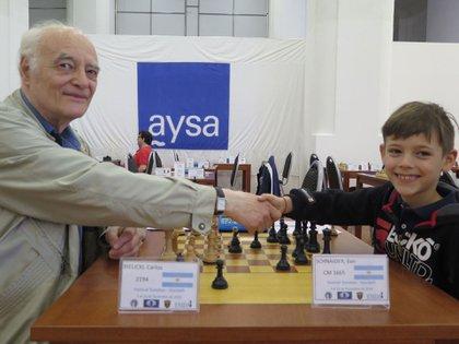 Ilan saluda a Carlos Bielicki (78), quien fue campeón mundial juvenil de ajedrez, en un torneo intergeneracional donde suelen cruzarse veteranos y niños