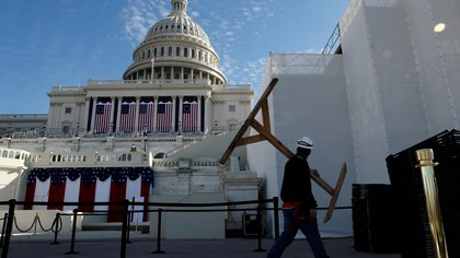 A worker cleans up the West Front of the U.S. Capitol and dismantles the inaugural platform and seating area the day after President Joe Biden was inaugurated as the 46th president of the United States on Capitol Hill in Washington, US, January 21, 2021. REUTERS/Jim Bourg