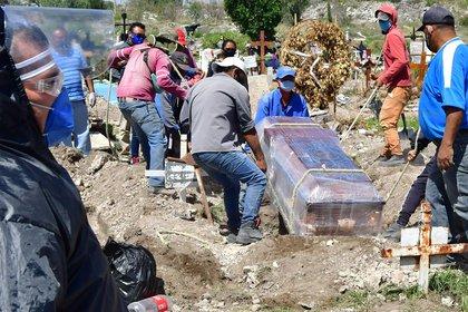 Trabajadores municipales fueron registrados el pasado jueves al introducir a una fosa un féretro desinfectado en el panteón de San Isidro, en el municipio de Ecatepec (México). EFE/Jorge Núñez