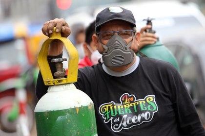 Un hombre con mascarilla hace cola junto a su botella de oxígeno, que quiere rellenar, en medio de la pandemia de coronavirus (APD)