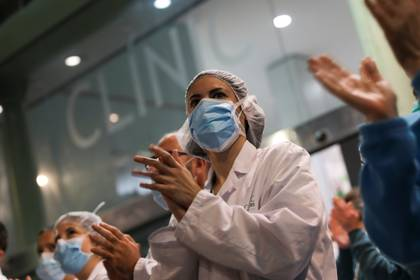 Los trabajadores de la salud del Hospital Clínico aplauden a los ciudadanos que les muestran su gratitud desde sus balcones y ventanas, durante el brote de la enfermedad coronavirus (COVID-19), en Barcelona, España, el 26 de marzo de 2020. (REUTERS/Nacho Doce)