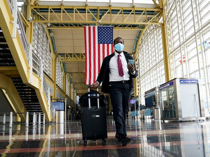 FILE PHOTO: A passenger walks through Reagan National airport as the novel coronavirus (COVID-19) pandemic continues to keep airline travel at minimal levels and the U.S. economy contracts in the first quarter at its sharpest pace since the Great Recession, in Washington, U.S. April 29, 2020.  REUTERS/Kevin Lamarque/File Photo