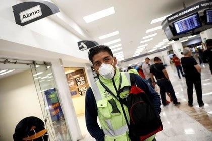 Un hombre usa una máscara facial protectora en el Aeropuerto Internacional Benito Juárez después de que el gobierno de México informó el viernes que había detectado los primeros casos de infección por coronavirus en el país. 28 de febrero de 2020. REUTERS / Carlos Jasso