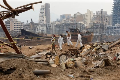 Miembros del equipo forense caminan cerca de los escombros en el lugar de la explosión del martes pasado, en la zona portuaria de Beirut, Líbano, 7 de agosto de 2020 (Reuters)