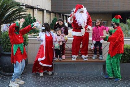 Un hombre vestido de Papá Noel entretiene a los niños en Beirut, Líbano (REUTERS/Mohamed Azakir)