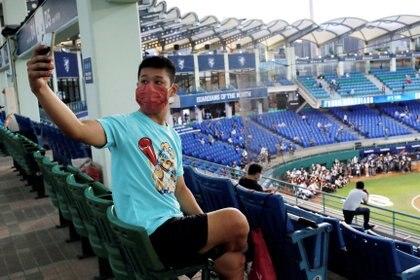 Un fanático del béisbol usa una máscara facial mientras se toma una selfie en el primer juego de la liga profesional que le permite al público desde el brote de COVID-19 en Taipei, Taiwán (Reuters)