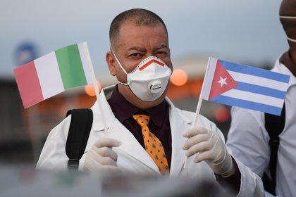 Un médico cubano con banderas de Italia y de su país (REUTERS/Daniele Mascolo)