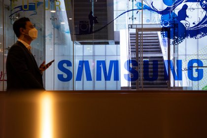 A man wearing a protective mask walks past the Samsung Electronics Co. signage at the company's D'light flagship store in Seoul, South Korea, on Tuesday, Oct. 6, 2020. Samsung were among a list of global firms that were cleared by India's Ministry of Electronics and Information Technology that won approval to manufacture products in India under a plan aimed at attracting investment of more than 10.5 trillion rupees ($143 billion) for mobile-phone production over the next five years. Photographer: SeongJoon Cho/Bloomberg