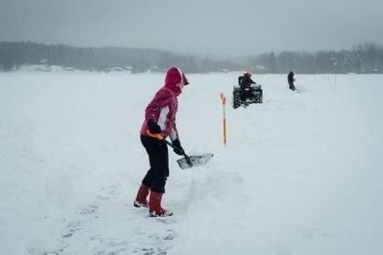 La gente quita la nieve a lo largo del perímetro de un carrusel de hielo que está en construcción para un intento de récord mundial en el lago congelado. (Alessandro RAMPAZZO / AFP)