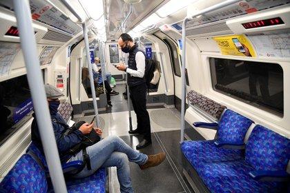 Pasajeros con mascarillas protectoras en un tren subterráneo durante la hora pico de la mañana, en medio del brote de la enfermedad por coronavirus, en Londres, Gran Bretaña (Reuters)