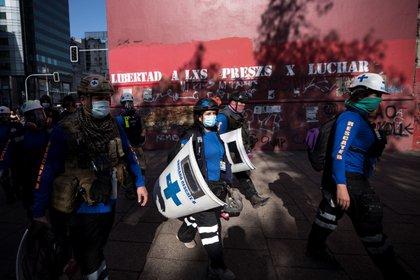 Un grupo de brigadistas de salud caminan durante una protesta contra el presidente de Chile, Sebastián Piñera, en el centro de Santiago (Chile). EFE/Alberto Valdés