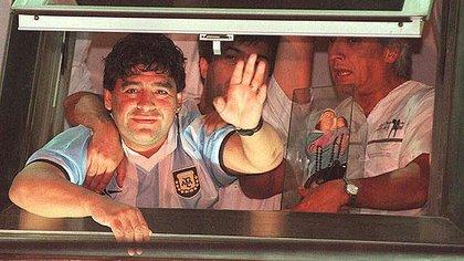 """Con la camiseta de la selección argentina firmada por Saviola, Maradona se asomó desde una habitación de la Clínica Sacre Coeur para saludar a la gente que rezaba por él y gritaba """"Diegooo, Diegoooo"""" (AP)"""