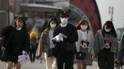 Visitors with masks leave Tokyo Disneyland in Urayasu, near Tokyo, Friday, Feb. 28, 2020. The amusement park will be closed from Feb. 29 until March 15 in an effort to prevent the spread of COVID-19. (AP Photo/Jae C. Hong)