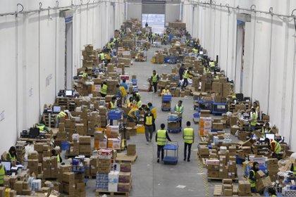Empleados de una empresa de logística en Wuhan separan paquetes durante un festival de comercio electrónico (Reuters)