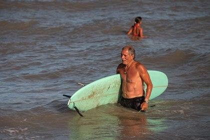 Feliz con su tabla, el señor deja las olas. El surf gana cada vez más adeptos de todas las edades