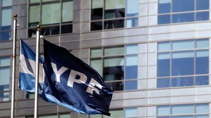 Una bandera de la empresa petrolera YPF ondea junto a una bandera argentina frente a la sede de YPF en Buenos Aires