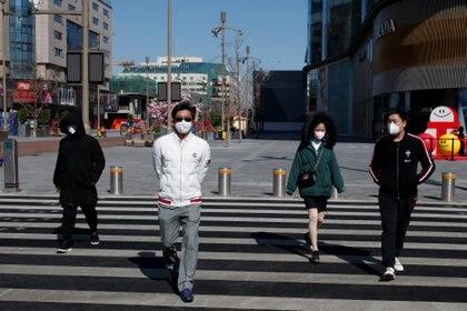 Personas con barbijo en una calle de Beijing (REUTERS/Thomas Peter)