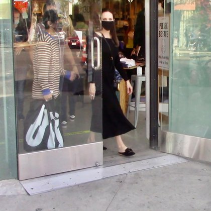 """Mientras paseaba por Hollywood, Angelina Jolie crosses se encontró con un grupo de activistas por los derechos de los animales. La actriz estaba de compras con uno de sus hijos en el local de Urban Outfitters cuando vio que integrantes de """"Rebels4Causes"""" manifestaban contra la piel y el cuero. Ella lució un look total black mientras que su hijo vestía una remera a rayas de colores"""