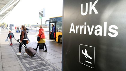Passengers disembark buses next to an arrivals sign at London Stansted Airport, operated by Manchester Airports Group (MAG), in Stansted, U.K., on Friday, Oct. 28, 2016. Ryanair Holdings Plc, Europe's biggest discount carrier, said the expansion of U.K. capacity is welcome but that the government should also have backed the expansion of Gatwick and its own base at London Stansted to meet travel demand for decades to come.