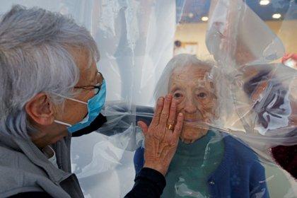 Marie-Paule y Marie-Josephe interactúan con su madre Colette, de 97 años, detrás de una lámina plástica removible dentro de una estructura de burbujas que permite a las familias dar abrazos sin riesgo de contaminación o transmisión de COVID-19, instalada en el refectorio de la Residencia. du Carre d'Or en el hospital Jeumont, mientras continúa el brote de coronavirus en Francia (REUTERS / Pascal Rossignol)