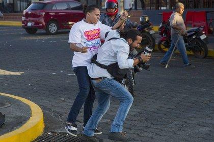 Un miembro de la juventud sandinista forcejea con el reportero gráfico de la agencia de noticias AP Alfredo Zuniga durante las protestas en contra de las reformas del Instituto Nicaragüense de Seguridad Social (INSS), en Managua(EFE/Jorge Torres)