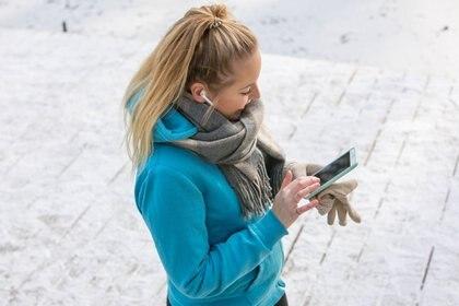 ILLUSTRATION - Eine junge Frau hoert am 22.01.2019 beim Joggen in einem Park in Hamburg Musik ueber ihr Smartphone (gestellte Szene). Foto: Christin Klose || Modellfreigabe vorhanden
