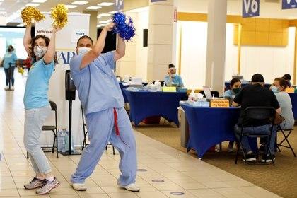 Dos enfermeras voluntarias bailan para darle la bienvenida a los jóvenes al vacunatorio de Chula Vista, California (REUTERS/Mike Blake)