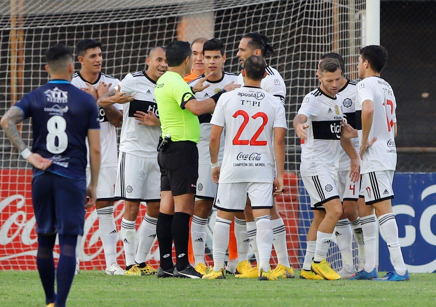 Jugadores de Olimpia reclaman una acción al árbitro Julio Quintana (c) hoy, en un partido del torneo Apertura paraguayo entre Olimpia y Guaireña FC en el estadio en Asunción (Paraguay). EFE/Nathalia Aguilar