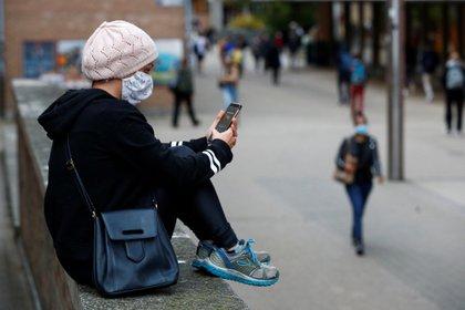 Una estudiante chequea su teléfono en la ciudad universitaria de Louvain-La-Neuve en Bélgica (Reuters)