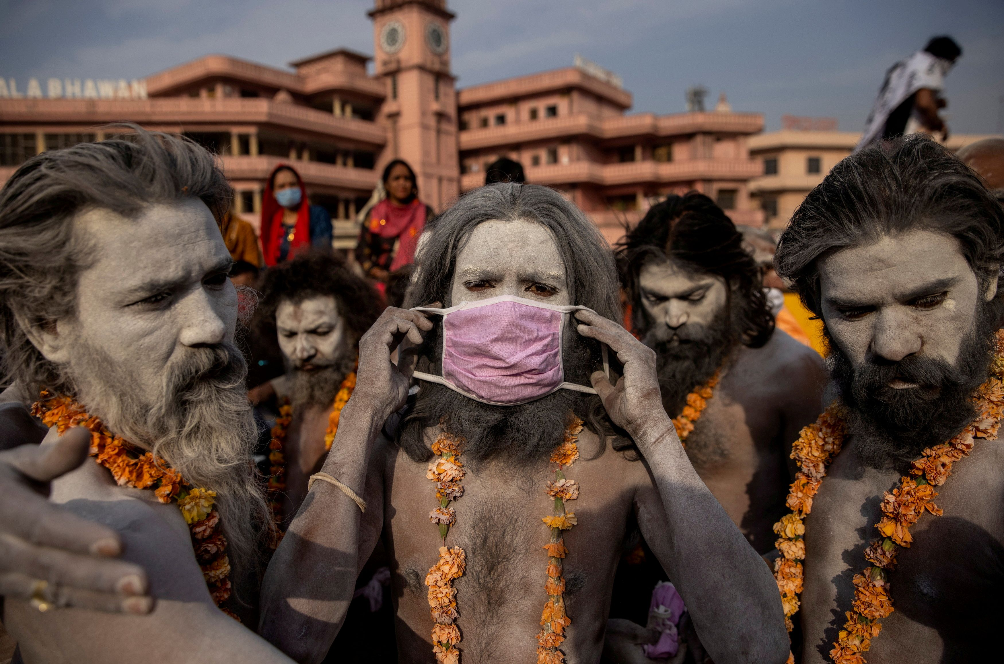 """Un Naga Sadhu, u hombre santo hindú lleva una máscara antes de la procesión para darse un baño en el río Ganges durante el Shahi Snan en el """"Kumbh Mela"""", o Festival de la Jarra, en medio de la propagación de la enfermedad del coronavirus (COVID-19), en Haridwar, India, el 12 de abril de 2021."""