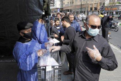 Milicianos Basiji entregan paquetes con elementos de protección contra el coronavirus a la salida de la estación del subte Meydane Valiasr de Teherán. (AFP)