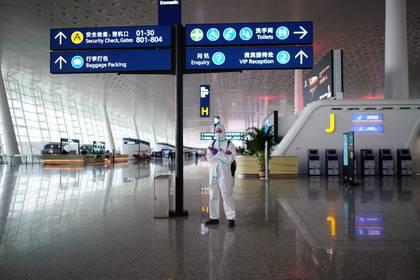 Un hombre con un traje protector está de pie en el Aeropuerto Internacional de Wuhan Tianhe después de que se levantara el bloqueo en la capital de la provincia de Hubei, epicentro del brote de coronavirus, el 10 de abril de 2020.  (REUTERS/Aly Song)