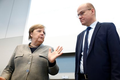Angela Merkel y el lider de la Unión Demócratacristiana (CDU), Ralph Brinkhaus, coversan antes de la reunión en el Parlamento de este martes   ( REUTERS/Michele Tantussi)
