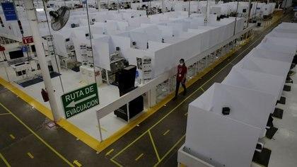 Imagen de archivo. Un empleado del fabricante estadounidense de autopartes Lear Corp., con una máscara facial protectora, pasa junto a los cubículos de trabajo provistos de divisiones como parte de las nuevas medidas de seguridad en la planta, antes de reanudar las operaciones durante el brote de la enfermedad por coronavirus (COVID-19), en Ciudad Juárez, México. 27 de mayo de 2020. Fotografía tomada el 27 de mayo de 2020. REUTERS / Jose Luis Gonzalez