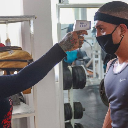 """Una instructora del gimnasio """"Evolution GYM"""" toma la temperatura a un usuario hoy antes de ingresar a las instalaciones, en la Ciudad de México. Los gimnasios reabren sus puertas al 30% de su capacidad y con cita previa ademas de estrictas medidas sanitarias por el COVID-19 (Foto: EFE)"""