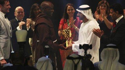 El príncipe de Dubái le entrega al premio al docente ganador. De fondo los otros finalistas (AP Photo)