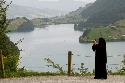 Imagen de archivo de una mujer vestida con un niqab tomando una fotografía junto al lago de Lungenersee, en el paso montañoso de Bruenigpass, en Suiza. 3 agosto 2017. REUTERS/Arnd Wiegmann
