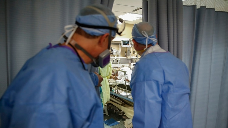 El Dr. Anthony Leno, Director de Medicina de Emergencia del Hospital St. Joseph's, a la izquierda, y el Dr. James Neuendorf, Director de Medicina, a la derecha, examinan una sala de examen donde un paciente con COVID-19 que sufrió un paro cardíaco fue revivido (AP/John Minchillo)