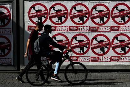 Foto de archivo. Gente pasa frenta a carteles que llaman a que Argentina no pague sus deudas, en Buenos Aires. 22 de febrero de 2020. REUTERS/Agustin Marcarian