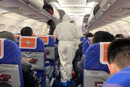 Trabajadores de la salud con trajes protectores verifican la condición de un pasajero en un avión que acaba de aterrizar desde Changsha, una ciudad en una provincia vecina al centro del brote de coronavirus, en Shanghái, China, el 25 de enero de 2020 (Reuters/ David Stanway)