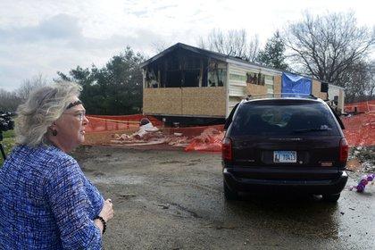 Una vecina observa los daños del incendio en el que murieron nueve personas (AP)
